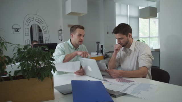 Pair of marketer looking on graphs and charts discussing results of sales video