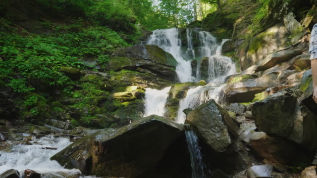 A pair of travelers with backpacks climbing over rocks to a beautiful waterfall video