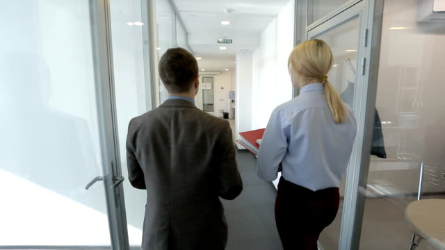 A pair pf colleagues are going throught the office and talking video
