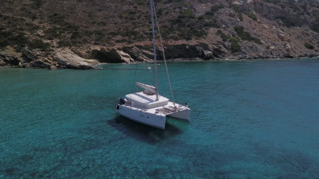 pair sunbathes on sailboat anchored in remote cove - 40 49 lat filmów i materiałów b-roll