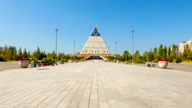 Palace of Peace and Accord in Astana Astana, Kazakhstan - August 25, 2016: Palace of Peace and Accord on a sunny day. On the outskirts of green plants and trees. People walk on the area. Timelapse 4K. kazakhstan stock videos & royalty-free footage