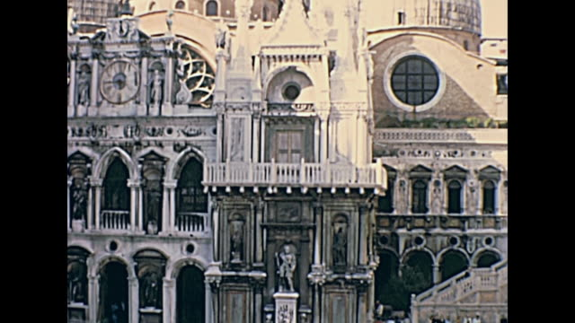 Palazzo Ducale internal Court Internal courtyard of Palazzo Ducale, Venice, Veneto, Italy on circa June 1967, San Marco Basilica facade and detail of external clock. Tourists in typical 60s clothes from historical archive footage. 20th century stock videos & royalty-free footage