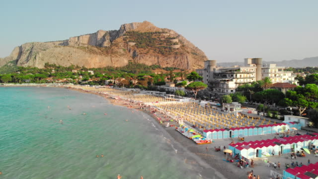 palermo, sicily, italy: the camera slides over ocean coastline. many vacationers and tourists on the beach. symmetrically arranged parasols from the sun. big rock on background. aerial drone shot - palermo città video stock e b–roll