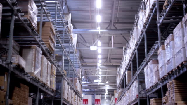 Palettes with cardboard boxes and materials on shelves in a storehouse, slow mo, dolly shoot video
