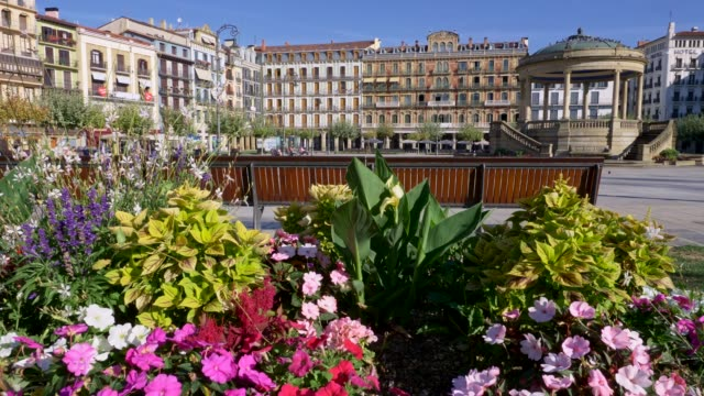 Pamplona, Spain. Bright colored flowers by a bench on a Plaza del Castillo. Lifting shot over flowers to get a wide view of the place. 4K