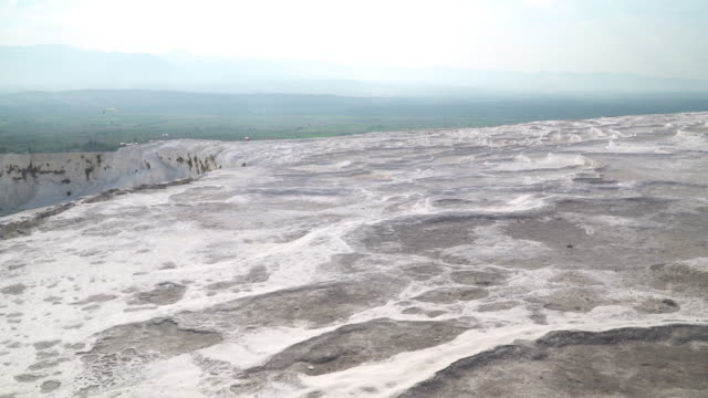 Pamukkale Pools without flowing water, droughts, and small village in summer. Panning view on Layers of travertines form terraces of carbonate minerals in Pamukkale, natural landmark of natural phenomena at Southwest Turkey.