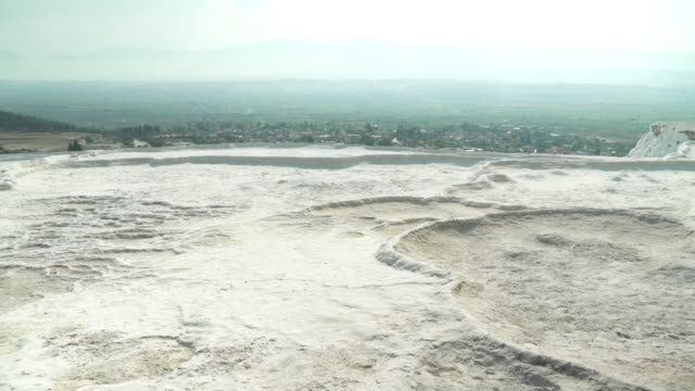 Pamukkale Pools without flowing water, droughts, in summer. Panning view on Layers of travertines form terraces of carbonate minerals in Pamukkale, natural landmark of natural phenomenon, on sunset at Southwest Turkey.