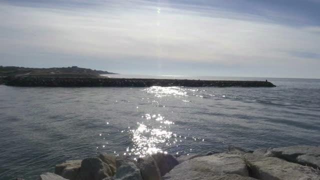 Pan across sunny Pamet Harbor jetties, waves slowly rolling in video