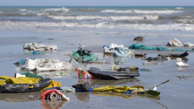 Pan close up shot of plastic garbage and trash on beach on sea background video