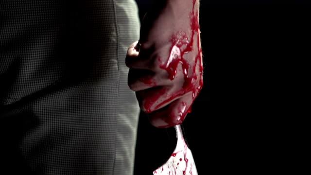 pan down of man holding bloody knife - vapen bildbanksvideor och videomaterial från bakom kulisserna