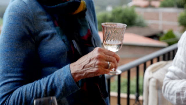Pan down of senior women's hands holding drinks outside on a terrace video