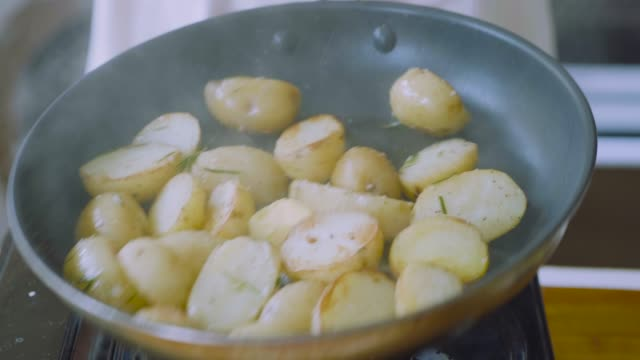 pan frying baby potato - patate video stock e b–roll