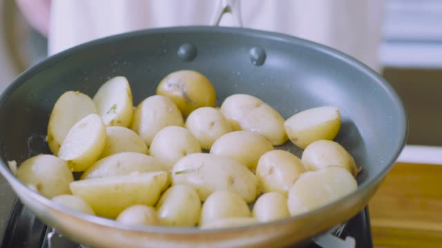 pan frying baby potato - молодой картофель стоковые видео и кадры b-roll