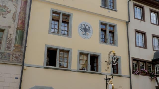 Pan left across marketplace in Stein am Rhein Camera pans left across the facades of historical buildings in the marketplace square. In Stein am Rhein, Switzerland. bay window stock videos & royalty-free footage