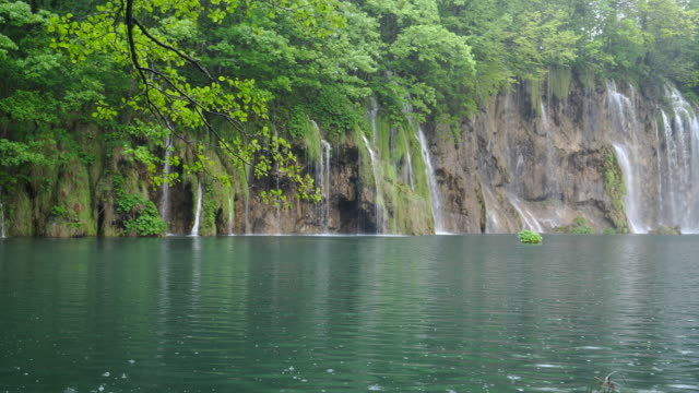 pan of a waterfall and lake at plitvice lakes national park on a rainy spring day