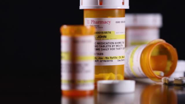 vídeos de stock, filmes e b-roll de bandeja de frascos e de comprimidos não-proprietários da medicina na superfície de madeira escura - garrafa
