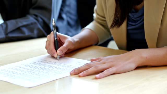 stockvideo's en b-roll-footage met pan of two people signing a contract - document