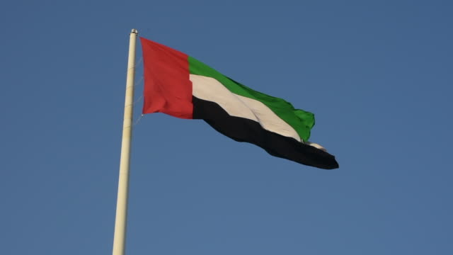 pan out view of a united arab emirates flag flying and waving in the sunshine with a deep blue sky background. - uae flag filmów i materiałów b-roll