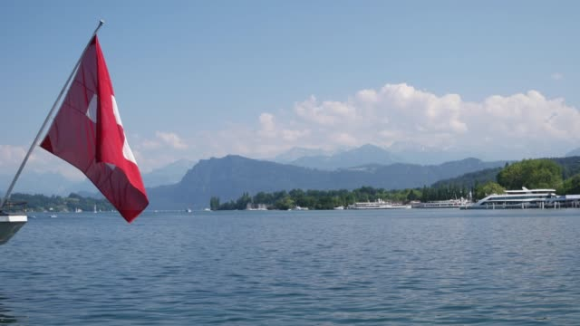 Pan right from Swiss flag on a boat to the Lucerne river in Lucerne, Switzerland