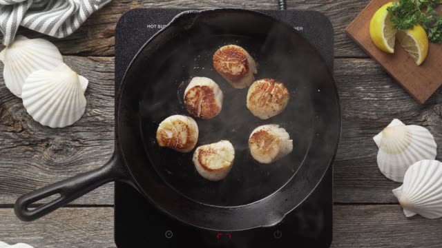 Pan Seared Scallops Overhead shot of delicious sea scallops cooking in a cast iron pan. animal shell stock videos & royalty-free footage