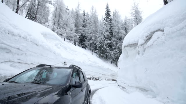Pan shot of a black suv parked in between high snow banks Pan shot of a black suv parked in between high snow banks vinter stock videos & royalty-free footage