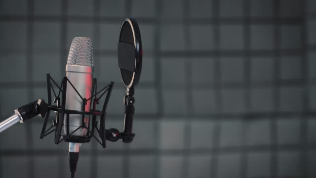 vídeos de stock, filmes e b-roll de pan shot de um microfone profissional para dublagem e dublagem no estúdio de gravação de som. close-up, conceito de podcasting - podcast