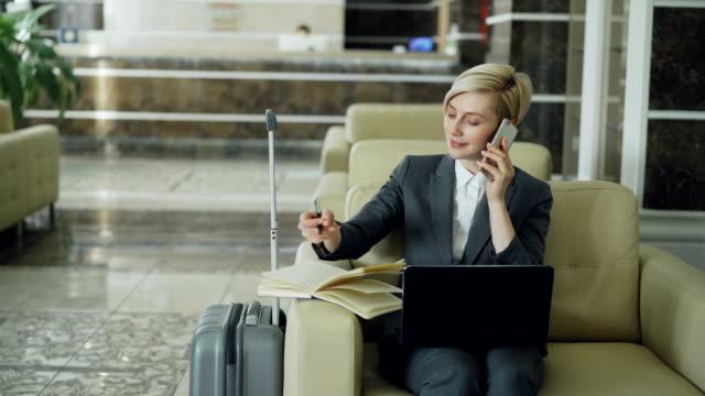 stockvideo's en b-roll-footage met pan schot van blonde drukke zakenvrouw zitten in fauteuil in de lobby van het hotel mobiele telefoon te praten, schrijven in kladblok en laptopcomputer gebruikt. business, reizen en mensen concept - business woman phone