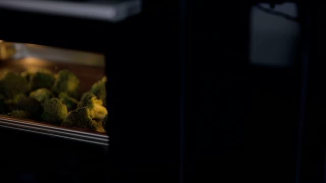 panoramica colpo di broccoli al forno a caldo - broccolo video stock e b–roll