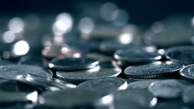 pan shot of close up money coin stacking on  the floor in dark light , business and financial for money saving or the investment background concept  , extremely close up and shallow DOF