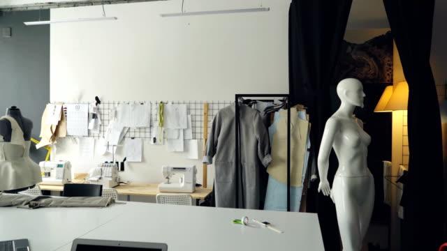 Pan-tir du studio de design de vêtements légers avec un bureau tailleur grand, mannequins, nombreuses esquisses épinglées sur le mur, les machines à coudre et les vêtements semi-fabriqués sur des rails. - Vidéo