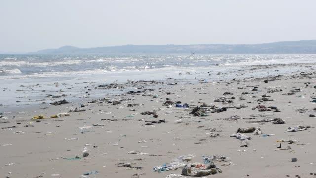 vídeos de stock e filmes b-roll de pan shot of plastic garbage and trash on the beach. static shot - oceano pacífico