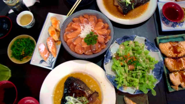 Pan Shot of Salmon, Salmon Burns and Roasted Chicken Japanese Food on the Table. Top View of Food. Pan Shot of Salmon, Salmon Burns and Roasted Chicken Japanese Food on the Table. Top View of Food. roast dinner stock videos & royalty-free footage