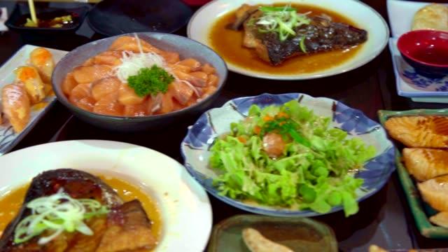 サーモンのパン、サーモンの火傷、ローストチキンの日本料理をテーブルに。食品の上面図。 ビデオ