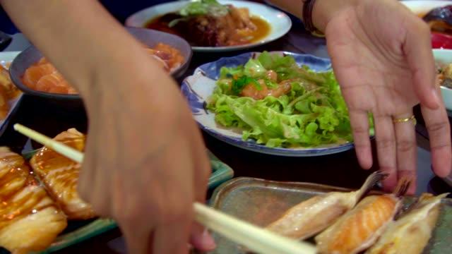 サーモンのパン、サーモンの火傷、ローストチキンの日本料理をテーブルに。食品の上面図。 - テーブル点の映像素材/bロール
