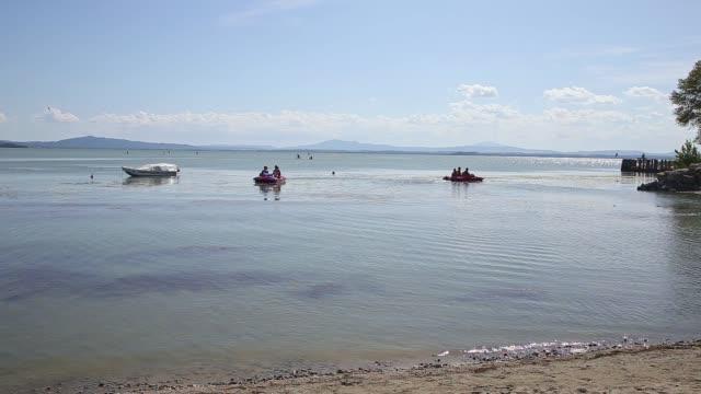 Pan shot of tourists on Sualzo beach and using pedalos on lake Trasimeno, Italy