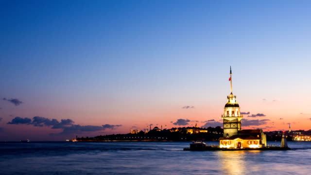 Pan shot timelapse of Maiden Tower or Kiz Kulesi with floating tourist boats on Bosphorus in Istanbul at night video