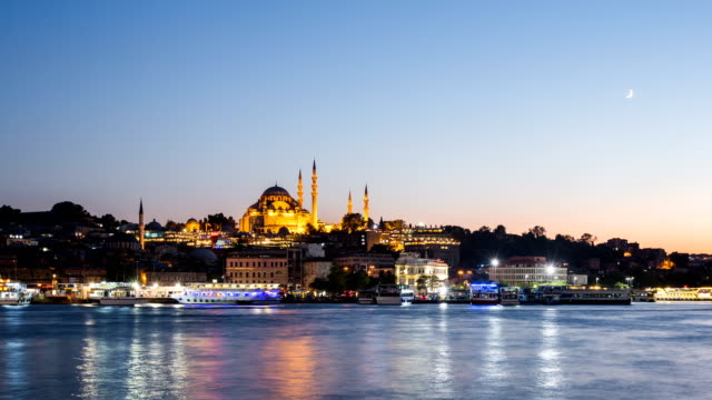 vídeos y material grabado en eventos de stock de timelapse de pan vista del paisaje urbano de istanbul con mezquita de süleymaniye con barcos turísticos flotando en el bósforo de noche - distrito eminonu