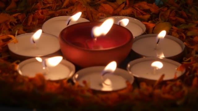 茶ライト蝋燭に囲まれて '光の祭り'、ディワリの diyas のマリーゴールドの花びらと銀のプレートにインドの陶製のランプをクローズ アップするパンがライトアップ - ディワリ点の映像素材/bロール