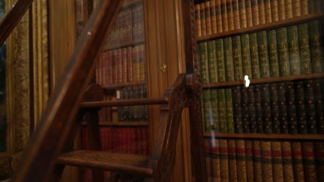 stockvideo's en b-roll-footage met pan omhoog oude bibliotheektreden en boeken - boekenkast