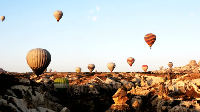 カッパドキアのウチヒサール城の背景を持つ妖精の煙突の上を飛んで、熱気球の panaromic ビュー - アナトリア点の映像素材/bロール
