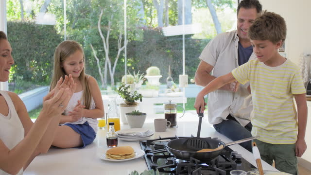 pancake flip with family in the kitchen - pancake video stock e b–roll