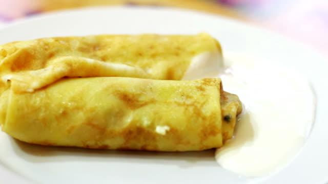 pfannkuchen mit sauerrahm auf einer platte im café - karotte peace stock-videos und b-roll-filmmaterial