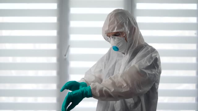 pandemic covid-19. portrait of a virologist in a protective suit. a male epidemiologist is ready to fight the infection - indumento protettivo video stock e b–roll