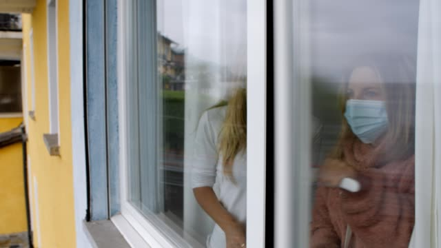 pandemic covid-19 quarantine- two women wearing medical face mask behind glass window looking out at the outdoors. stay home stay safe people preventing coronavirus - hand on glass covid video stock e b–roll