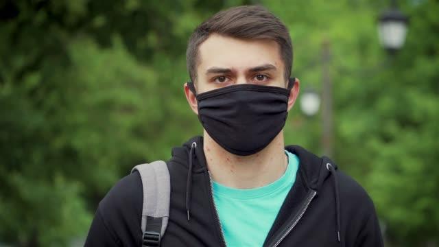 pandemie, porträt eines jungen touristen mit schutzmaske auf der straße. n1h1 coronavirus quarantäne, virenschutz - menschliches gelenk stock-videos und b-roll-filmmaterial