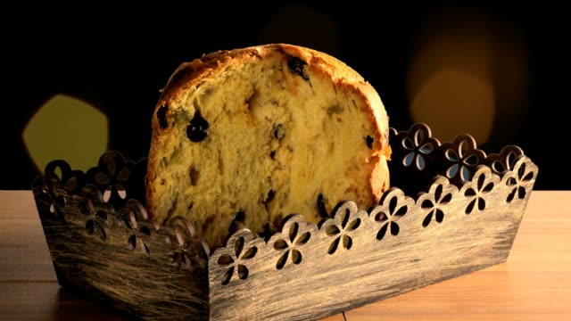 panettone on wooden table, background with flashing bokeh lights - panettone video stock e b–roll