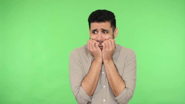Panicked scared brunette man biting nails to relieve anxiety or stress. green background, chroma key