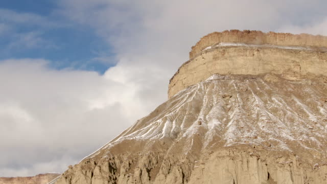 Panning Aerial Drone Shot of the Striped, Eroded Sandstone Cliffs of the Bookcliffs (Geological Formation) and Mt. Garfield in the High Desert of Grand Junction and Palisade, Colorado on a Snowy, Partially Cloudy Day