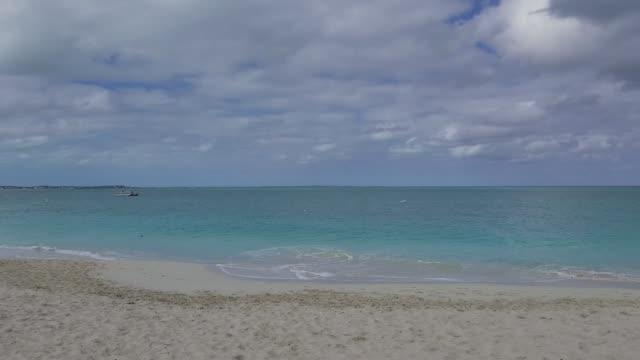 stockvideo's en b-roll-footage met pannen langs strand tijdens een bewolkte dag in grace bay, providenciales, turks- en caicoseilanden - providenciales