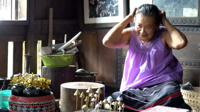 panning and focus: thai grandmother dressed with a ancient hand-made hairpin - аксессуар для волос стоковые видео и кадры b-roll